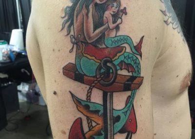 Mom and baby mermaids sitting on an anchor tattoo in color - by Jared - Maui Tattoo Artist at Mid-Pacific Tattoo