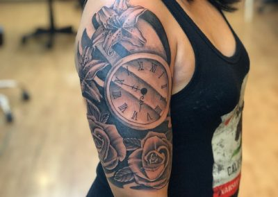 Black and grey clock with roses and lilies tattoo - by Buge - Maui Tattoo Artist at Mid-Pacific Tattoo