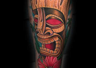 Hawaiian Tiki statue with red eyes and a red hibiscus tattoo - by Matt - Maui Tattoo Artist at Mid-Pacific Tattoo