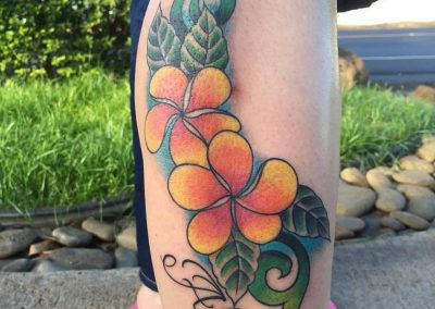 Orange plumerias with lettering tattoo  - by Jared - Maui Tattoo Artist at Mid-Pacific Tattoo