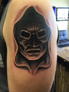 A metal mask in a hood tattoo - by Curtis - Maui Tattoo Artist at Mid-Pacific Tattoo