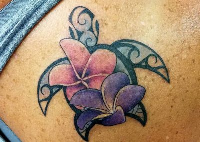 Polynesian style turtle tattoo with pink and purple plumerias - by Bry - Maui Tattoo Artist at Mid-Pacific Tattoo